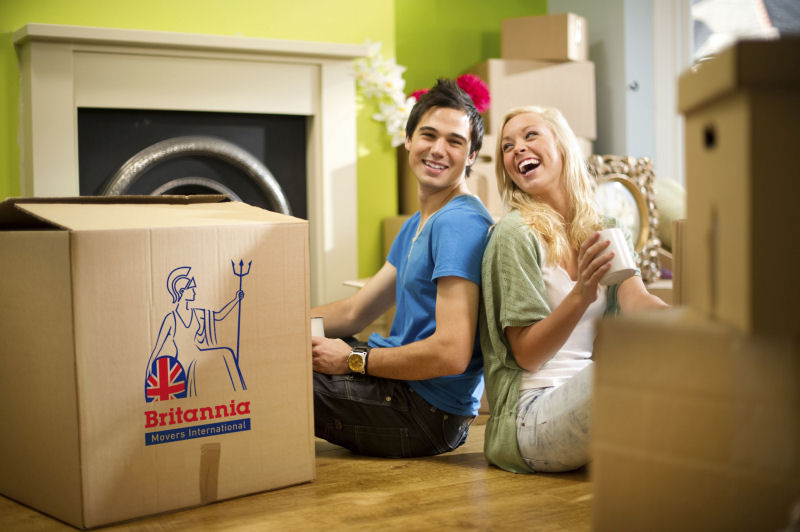 Happy couple sitting on the floor in the lounge surrounded by removal boxes