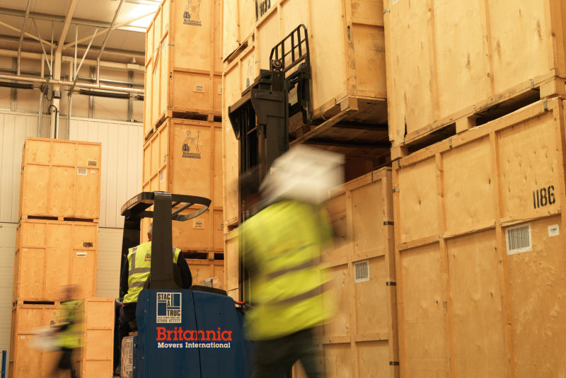Busy Britannia storage warehouse with reach truck in operation and porters carrying boxes