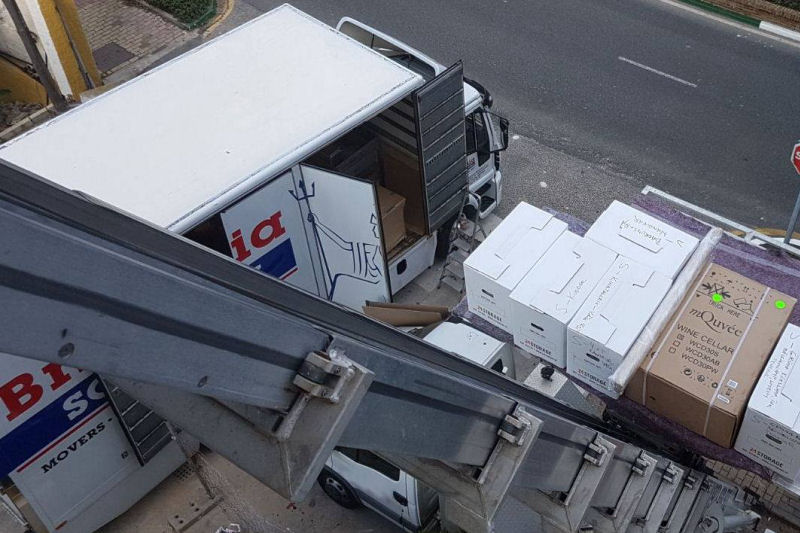 Aerial view of external furniture lift in operation in Estepona