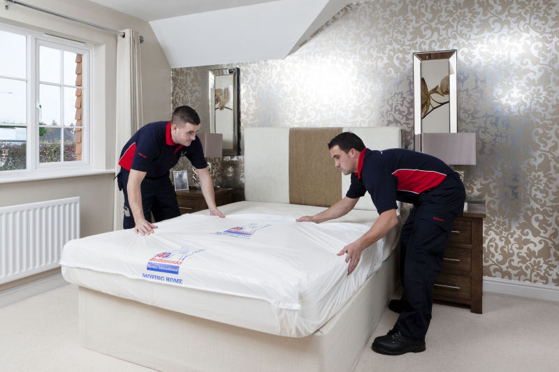 Two Britannia porters placing a polythene cover over a matress